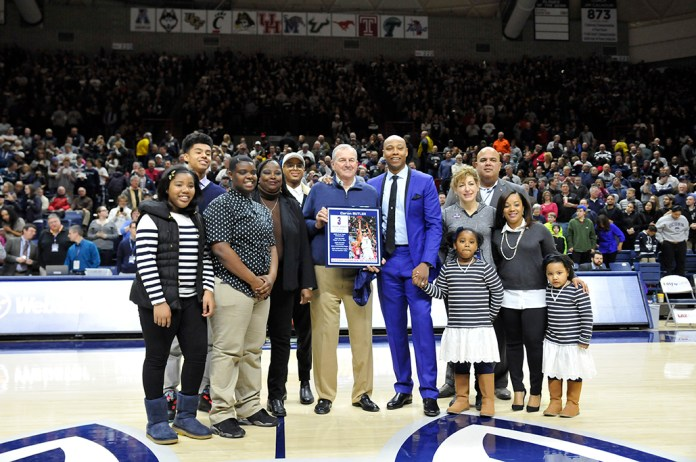Caron Butler (seventh from the left) accepts a plaque as he enters the Huskies of Honor. He is joined on the court at Gampel Pavilion by his family, former coach Jim Calhoun, UConn President Susan Herbst, and athletic director Warde Manuel. (Jason Jiang/The Daily Campus)