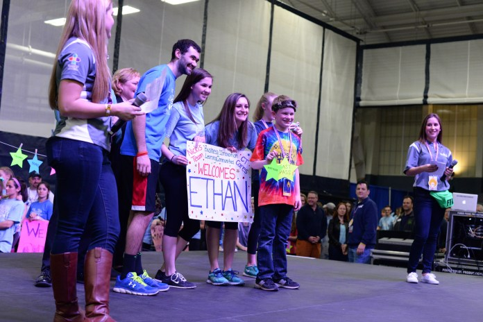 The team of Igor Lekontsev, the HuskyTHON dancer who received the $1,989 donation, stands on stage with their HuskyTHON child at the beginning of the dance marathon for Connecticut Children's Medical Center. (Amar Batra/The Daily Campus)
