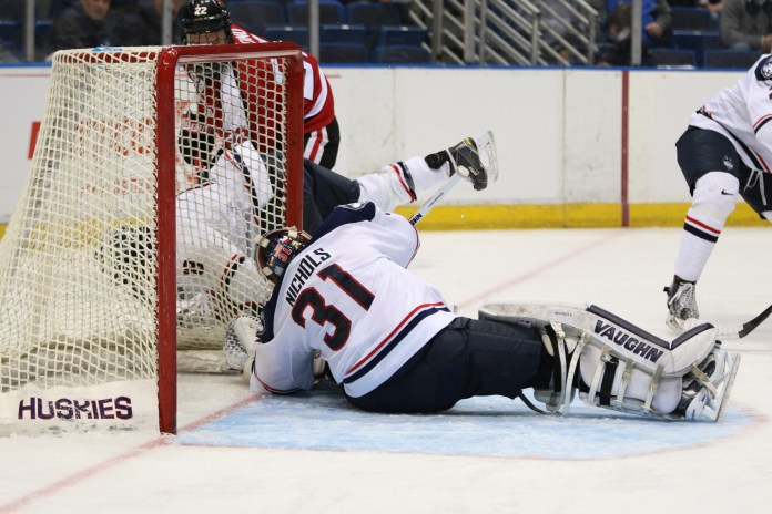 UConn men's ice hockey goalie Rob Nichols tries to keep a Northeastern shot out of the net during the Huskies' game at the XL Center in Hartford, Connecticut on Friday, Feb. 19, 2016. Nichols was pulled in the first period after allowing four Northeastern goals. (Tyler Benton/The Daily Campus)