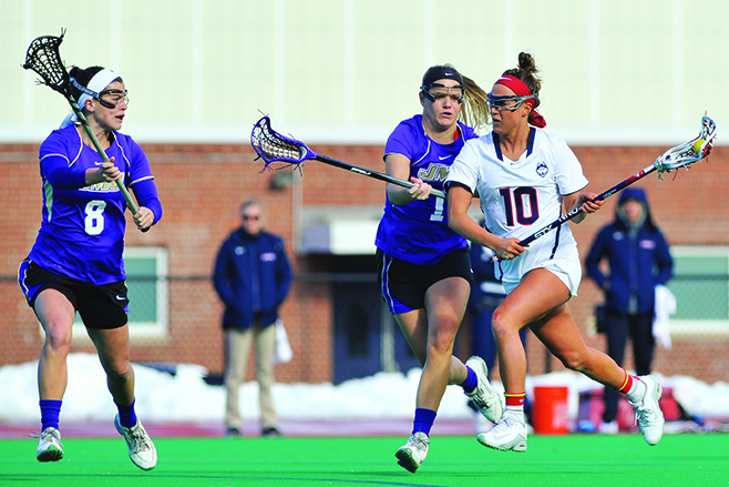 Grace Nolan (10) races by two James Madison defenders during UConn's 12-10 victory at the George J. Sherman Family Sports Complex on Sunday Feb. 21, 2016. Nolan, a sophomore attacker, has 8 goals on the year. (Jason Jiang/The Daily Campus)