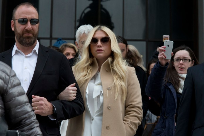 Pop star Kesha, center, leaves Supreme court in New York, Friday, Feb. 19, 2016. Kesha is fighting to wrest her career away from a hitmaker she says drugged, sexually abused and psychologically tormented her _ and still has exclusive rights to make records with her. Producer Dr. Luke says the singer is slinging falsehoods and ruining his reputation to try to weasel out of her recording contract and strike a new deal. (AP)