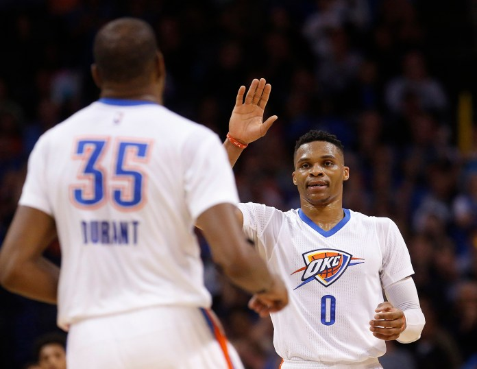 Oklahoma City Thunder guard  Russell  Westbrook (0) high-fives teammate Kevin Durant (35) during the third quarter of an NBA basketball game against the Houston Rockets in Oklahoma City, Tuesday, March 22, 2016. Oklahoma City won 111-107. (AP Photo/Sue Ogrocki)