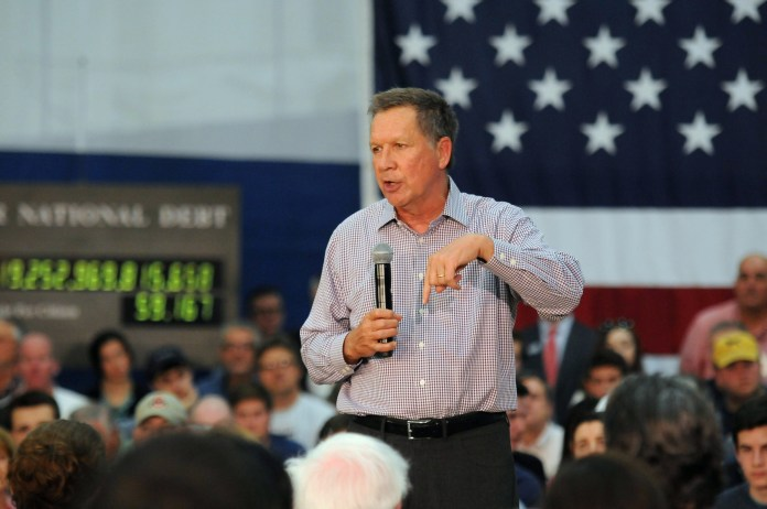 Republican presidential candidate John Kasich tells the crowd of about 1,500 people in Glastonbury on Friday, April 22, 2016, that rapid job growth only happens when the number on the debt clock behind him goes down.  (Kyle Constable/The Daily Campus)
