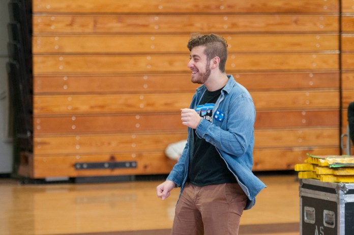 """Harper Wise, a senior at Fairfield Warde High School, dances as he welcomes attendees to Democratic presidential candidate Hillary Clinton's rally at the University of Bridgeport on Sunday, April 24, 2016. He said he supports Clinton because """"she's a rock star"""" and added that he is excited to cast his first-ever vote for her. (Kyle Constable/The Daily Campus)"""