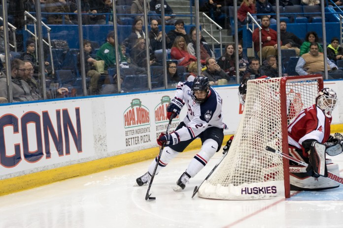 Freshman forward Max Letunov skates behind the net during a game against Northeastern on Friday, Feb. 19 at the XL Center in Hartford. Letunov led the team with 40 points, 24 assists and 16 goals. He was a big factor in the Huskies' 11-21-4 season that saw them host a Hockey East playoff tournament.(Tyler Benton/The Daily Campus)
