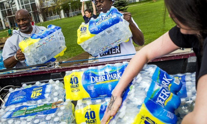 Flint residents Arthur Woodson, left, and Wade Garvins fill the bed of a pickup truck with water for a Flint resident in need as more than 50 people protest in front of City Hall in downtown Flint, Mich., Monday, April 25, 2016. Protesters show their continued disdain on the two-year anniversary of the date the drinking water source was switched to the Flint River. (Jake May/The Flint Journal-MLive.com via AP)