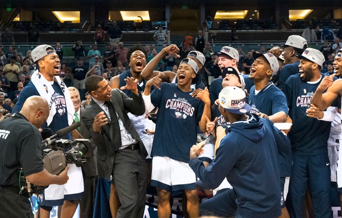 The UConn men's basketball team celebrates with head coach Kevin Ollie after winning the American Athletic Conference Championship at the Amway Center in Orlando, Florida on Sunday, March 13, 2016. Their 72-58 win over Memphis clinched UConn's automatic bid to the NCAA tournament. (Ashley Maher/The Daily Campus)