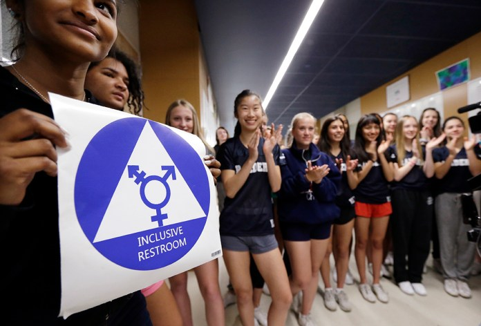 Deena Kennedy, left, holds a sticker for a new gender neutral bathroom as members of the cheer squad applaud behind during a ceremonial opening for the restroom at Nathan Hale high school Tuesday, May 17, 2016, in Seattle. President Obama's directive ordering schools to accommodate transgender students has been controversial in some places but since 2012 Seattle has mandated that transgender students be able to use of the bathrooms and locker rooms of their choice. Nearly half of the district's 15 high schools already have gender neutral bathrooms and one high school has had a transgender bathroom for 20 years. (AP Photo/Elaine Thompson)