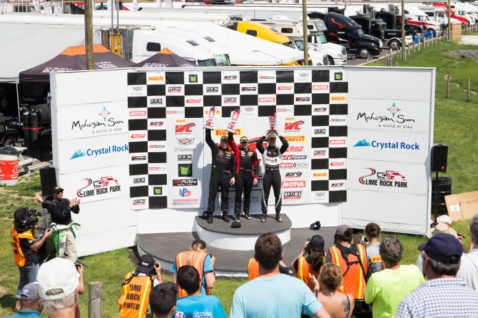 The top three drivers from the GTS race stand atop the podium. The cars are separated into categories based on several factors, including size, horsepower, and more.(Jackson Haigis/Daily Campus)
