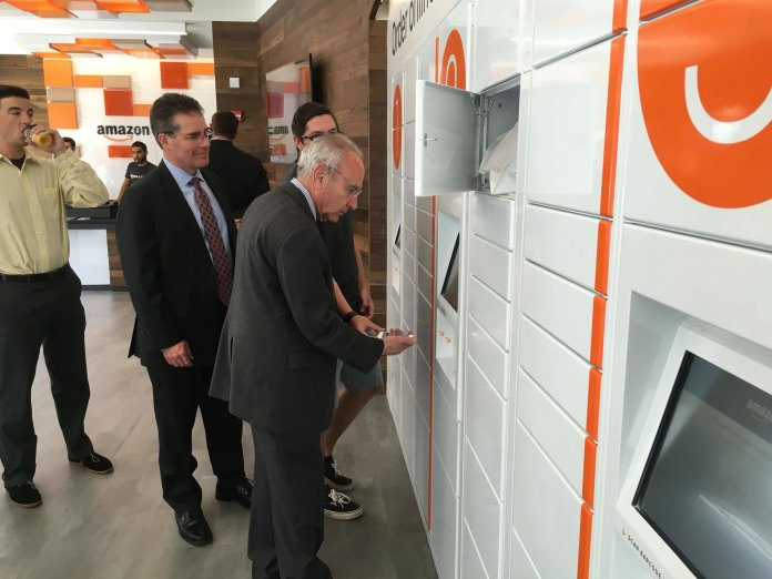 Amazon@Storrs campus associate Kasey Pekala (right) gives Mansfield mayor Paul Shapiro (front)a tutorial in using the Amazon@Storrs kiosk. (Chris McDermott/Daily Campus)