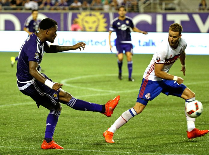Orlando City's  Cyle  Larin , left, takes a shot on goal past Toronto FC's Josh Williams during the second half of an MLS soccer game, Wednesday, Aug. 24, 2016, in Orlando, Fla. Toronto FC won 2-1. (John Raoux/AP)