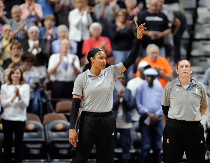 Minnesota Lynx' Maya  Moore , left, and Lindsay Whalen are acknowledged by fans for their gold medal win in the Olympics, at the start of a WNBA basketball game against the Connecticut Sun, Friday, Aug. 26, 2016, in Uncasville, Conn. (AP Photo/Jessica Hill)