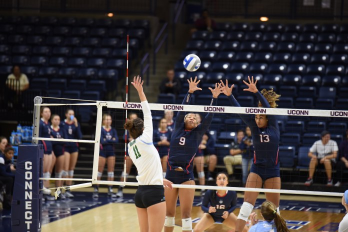 Outside hitter Camille Evans blocks alongside middle hitter Tosin Adeniyi in a game against Tulane on Sunday, Sept. 25, 2016. (Zhelun Lang/The Daily Campus)