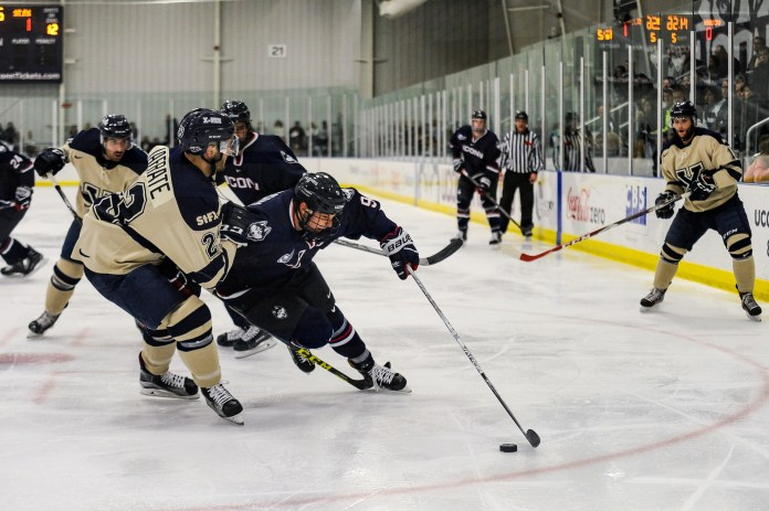 Freshman forward Alexander Payusov attempts to outmaneuver an X-Men defender during the Huskies 4-3 loss to St. Francis-Xavier. (Jason Jiang/The Daily Campus)