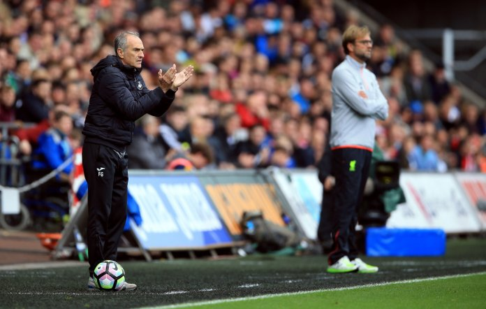 Swansea City manager Francesco Guidolin encourages his players, with Liverpool's manager Jurgen Klopp, right, during their English Premier League soccer match at the Liberty Stadium,Swansea, England, Saturday Oct. 1, 2016. (Nigel French / PA via AP)