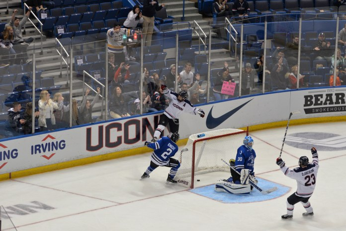 Kasperi Ojantakanen (#23) celebrates in front of the net after Spencer Naas (#8) scores a goal on UAH goaltender Matt Larose (#30) at the XL Center in Hartford, Conn. on Saturday Oct. 8, 2016. (Amar Batra/The Daily Campus)
