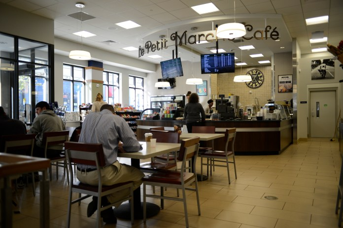 """UConn students and faculty enjoy an afternoon café visit to the new Starbucks in the UConn bookstore on Wednesday, Oct. 12 2016. The sign remains unchanged from the previous café, """"Le Petit Marche."""" (Jason Jiang/The Daily Campus)"""