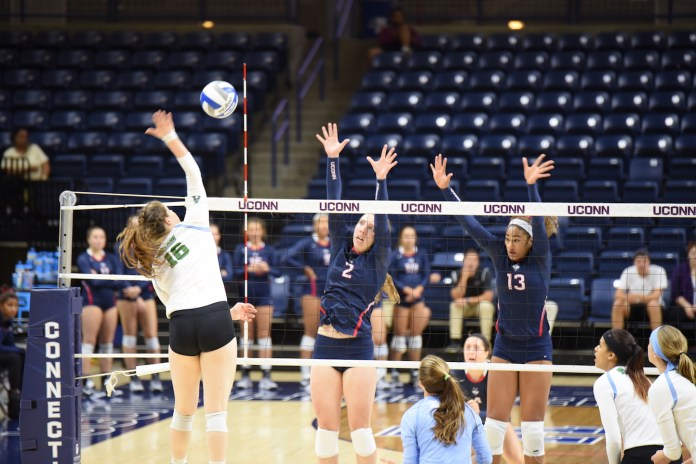 UConn juniors Danielle Cabell (#2) and Tosin Adeniyi (#13) jump to block an attempt from Tulane's Hannah Shaw (#16) in a game at Gampel Pavilion on Sunday Sep. 25, 2016. The Huskies won 3-1. (Zhelun Lang/The Daily Campus)
