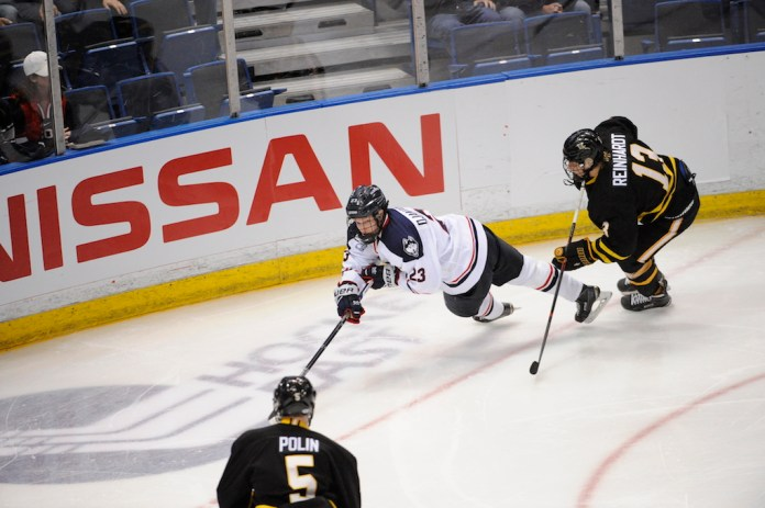UConn's Kasperi Ojantakanen (#23) dives for a puck against American International on October 21st. (Tyler Benton/The Daily Campus)
