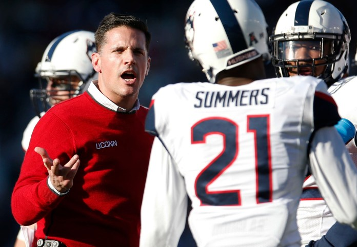 Connecticut head coach Bob Diaco, left, talks with cornerback Jamar Summers (21) during the first half of an NCAA college football game against Boston College in Boston, Saturday, Nov. 19, 2016. Boston College won 30-0. (AP Photo/Michael Dwyer)