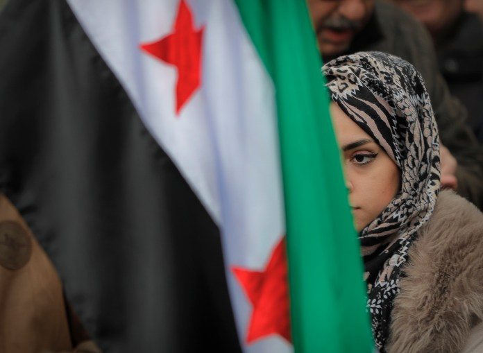 A female of the Syrian community stands behind Syria's flag during a protest outside Syria's embassy in Bucharest, Romania, Friday, March 17, 2017. Syrians mark the sixth anniversary of the country's bitter civil war, which has killed more than 400,000 people and displaced millions of others. (Vadim Ghirda/AP Exchange)