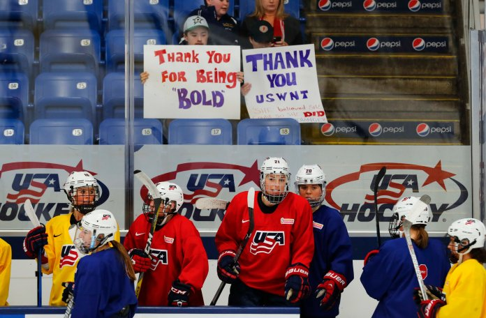 United States teammates practice with fans holding support signs in preparation for the IIHF Women's World Championship hockey tournament, Thursday, March 30, 2017, in Plymouth, Mich.USA Hockey and the women's national team agreed to a contract Tuesday night that ended a wage dispute. (AP Photo/Paul Sancya)