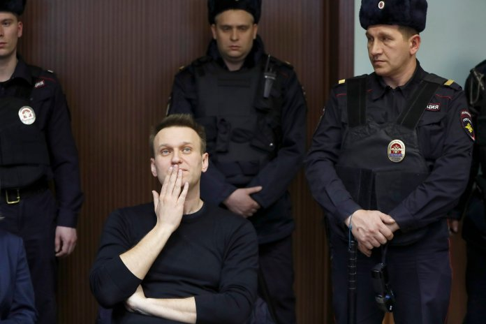 Russian opposition leader Alexei Navalny listens to a sentence in court in Moscow, Russia, Thursday, March 30, 2017. Russian President Vladimir Putin has rejected Western calls for the release of jailed protesters, including opposition leader Alexei Navalny, in his first public comments about a wave of nationwide rallies against government corruption. (AP Photo/Pavel Golovkin)