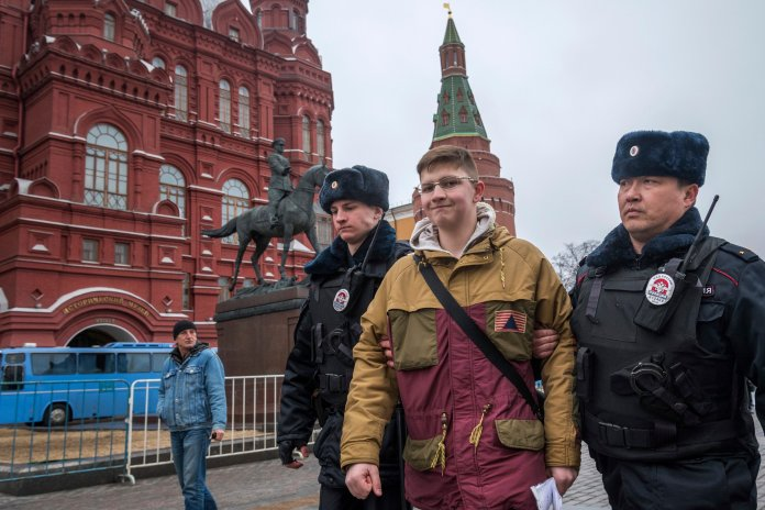 Police officers detain a school boy in front of the Historical Museum near Red Square in anticipation of a possible opposition action in Moscow, Russia, Sunday, April 2, 2017.(AP Photo/Ilya Varlamov)