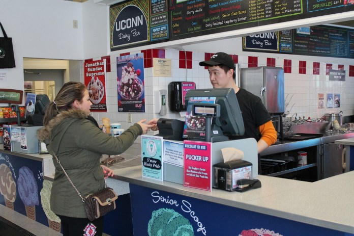 Shin Soyoma, a 6th semester Nutritional Sciences major, serves a customer.No sad and terrible grocery store popsicle can compare to the fabulous creamery concoctions dreamed up by the UConn Dairy Bar. (Kelley Huber/The Daily Campus)