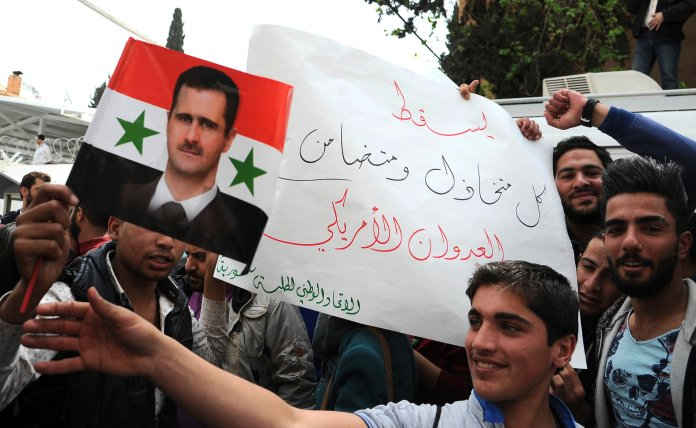 """In this photo released by the Syrian official news agency SANA, pro-government protesters hold a portrait of President Bashar Assad and a placard that reads, """"Down with everyone who cooperated and supported the American aggression,"""" during a protest in front of the the United Nations building, in Damascus,Syria, Tuesday, April 11, 2017. (SANA via AP)"""