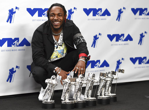 """Kendrick Lamar poses in the press room with the awards for best hip hop video, best direction, best cinematography, best art direction, best visual effects, and video of the year for """"HUMBLE."""" at the MTV Video Music Awards at The Forum on Sunday, Aug. 27, 2017, in Inglewood, Calif. (Photo by Jordan Strauss/Invision/AP)"""