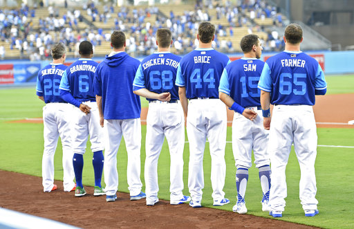 Members of the Los Angeles Dodgers stand for the National Anthem prior to a baseball game against the Milwaukee Brewers, Friday, Aug. 25, 2017, in Los Angeles. As part of MLB's Players Weekend, teams are wearing special uniforms designed to evoke the game at its more youthful levels like little league. (AP Photo/Mark J. Terrill)