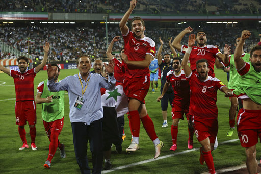 Syria's national soccer team celebrates at the conclusion of their match with Iran which drew 2-2 during their Round 3 - Group A World Cup qualifier at the Azadi Stadium in Tehran,Iran, Tuesday, Sept. 5, 2017. (AP Photo/Vahid Salemi)