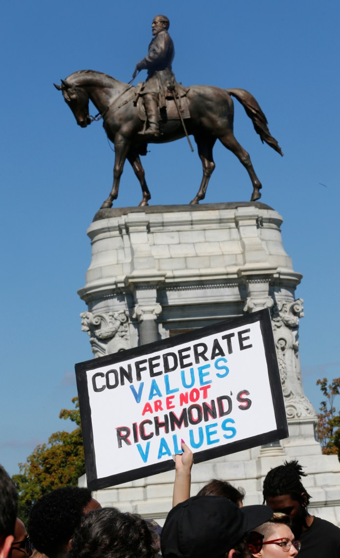 Counter protesters hold signs in front of the statue of Confederate General Robert E. Lee on Monument Avenue in Richmond, Va., Saturday, Sept. 16, 2017. (Steve Helber/AP)