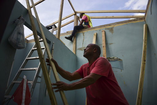 Pedro Deschamps helps workers hired by FEMA to carry out the installation of a temporary awning roof at his house, which suffered damage during Hurricane Maria, in San Juan,Puerto Rico, Wednesday, Nov. 15, 2017. (AP Photo/Carlos Giusti)