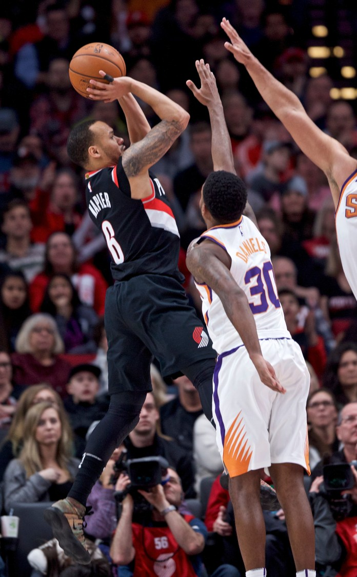 Portland Trail Blazers guard Shabazz Napier, left, shoots over Phoenix Suns guard Troy Daniels during the second half of an NBA basketball game in Portland, Ore., Tuesday, Jan. 16, 2018. (AP Photo/Craig Mitchelldyer)