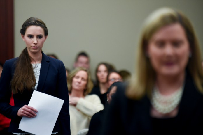 """Rachael Denhollander, left, is introduced by Assistant Attorney General Angela Povaliatis, before she makes the final victim impact statement, during Larry Nassar's sentencing hearing Wednesday, Jan. 24, 2018 in Lansing, Mich. The former sports doctor who admitted molesting some of the nation's top gymnasts for years was sentenced Wednesday to 40 to 175 years in prison as the judge declared: """"I just signed your death warrant.""""(Matthew Dae Smith/AP)"""