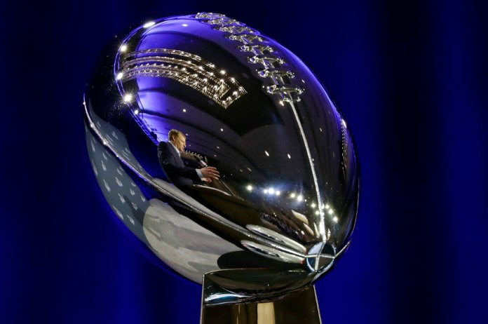 NFL Commissioner Roger Goodell is reflected in the Vince Lombardi Trophy as he speaks during a news conference in advance of the Super Bowl 52 football game, Wednesday, Jan. 31, 2018, in Minneapolis. The Philadelphia Eagles play the New England Patriots on Sunday, Feb. 4, 2018. (AP Photo/Matt Slocum)