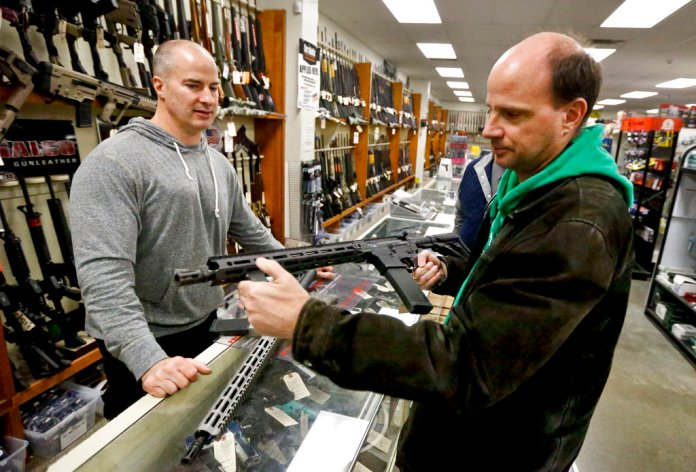 Wes Morosky, owner of Duke's Sport Shop. left, helps Ron Detka as he shops for a rifle on Friday, March 2, 2018, at his store in New Castle.(AP Photo/Keith Srakocic)