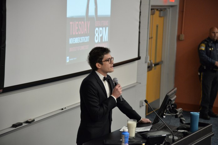 """Controversial conservative reporter Lucian Wintrich attempts to give a lecture titled """"It's Okay to Be White"""" on Tuesday, Nov. 28, 2017.Wintrich was drowned out by protestors and was subsequently arrested after assaulting a protestor. (Amar Batra/The Daily Campus)"""