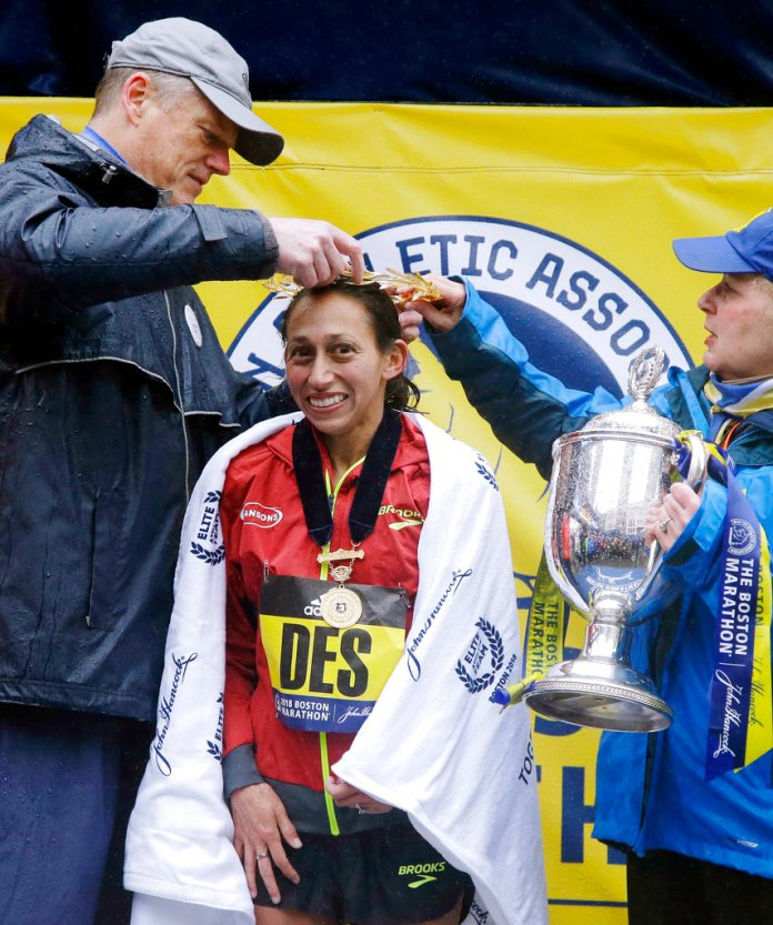 Massachusetts Gov. Charlie Baker, left, places the victor's crown on Desiree Linden, of Washington, Mich., after she won the women's division of the 122nd Boston Marathon on Monday, April 16, 2018, in Boston. She is the first American woman to win the race since 1985. (AP Photo/Elise Amendola)