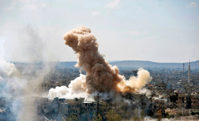 In this photo released by the Syrian official news agency SANA, smoke rises after Syrian government airstrikes and shelling hit in Hajar al-Aswad neighborhood held by Islamic State militants, southern Damascus, Syria, Sunday, April 22, 2018. Syrian state media says government forces are pounding districts of southern Damascus held by Islamic State militants with warplanes, helicopters and artillery in a bid to enforce an evacuation deal reached earlier in the week. (SANA via AP)
