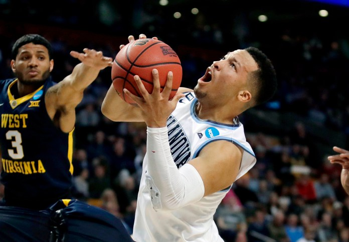 FILE - In this March 23, 2018, file photo, Villanova's Jalen Brunson, right, drives against West Virginia's James Bolden (3) during the first half of an NCAA men's college basketball tournament regional semifinal, in Boston. Brunson, The Associated Press men's college basketball player of the year, has declared for the NBA draft after winning two national titles at Villanova. (AP Photo/Charles Krupa)