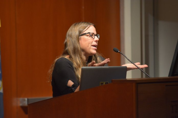 Meredith Stern addresses the crowd about combining art with social justice projcets in the Konover Auditorium on Sept. 7 (Nicholas Hampton/ The Daily Campus)