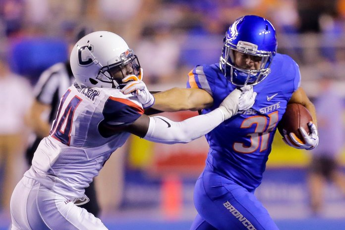 Boise State running back Skyler Seibold pushes away from the tackle attempt by Connecticut defensive back Tahj Herring-Wilson.(AP Photo/Steve Conner)