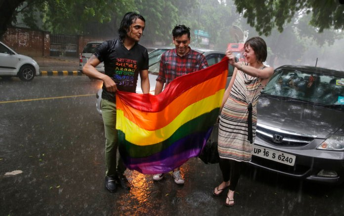Supporters and gay rights activists celebrate amid heavy downpour after the country's top court struck down a colonial-era law that made homosexual acts punishable by up to 10 years in prison, in New Delhi, India, Thursday, Sept. 6, 2018. The court gave its ruling Thursday on a petition filed by five people who challenged the law, saying they are living in fear of being harassed and prosecuted by police. (AP Photo/Altaf Qadri)