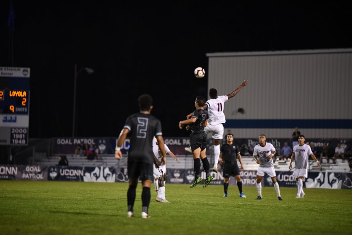 Abdou Mbacke Thiam skies for a header chance. (Charlotte Lao/ The Daily Campus)
