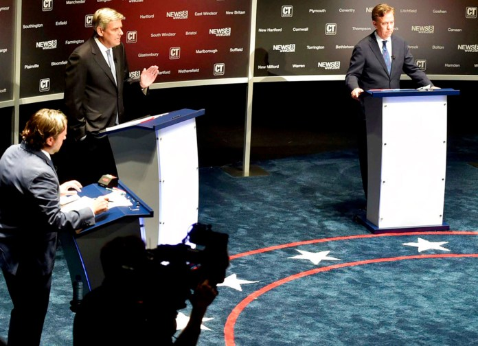 Gubernatorial candidates, Republican Bob Stefanowski, center, and Democrat Ned Lamont, right, participate in a debate at the Shubert Theatre in New Haven, Conn., Monday, Sept. 17 2018. Host and moderator Michael Barbaro is at left. (Peter Hvizdak/New Haven Register via AP)