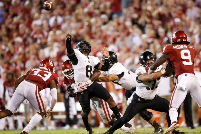 Army quarterback Kelvin Hopkins Jr. gets hit by Oklahoma defensive lineman Kenneth Mann while passing during a game in Norman, Oklahoma. (Ian Maule/Tulsa World via AP)