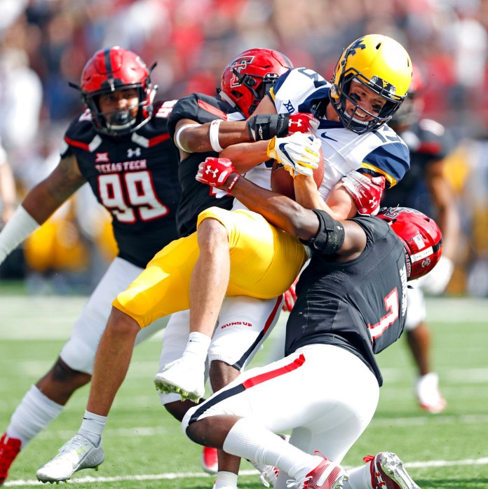 West Virginia's David Sills V (13) is tackled by Texas Tech's Jah'Shawn Johnson (7) during the first half of an NCAA college football game Saturday, Sept. 29, 2018, in Lubbock, Texas. (AP Photo/Brad Tollefson)